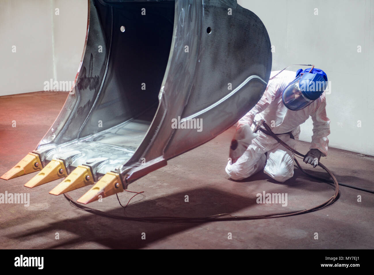 Spray painter painting digger bucket in spray booth in engineering factory - Stock Image