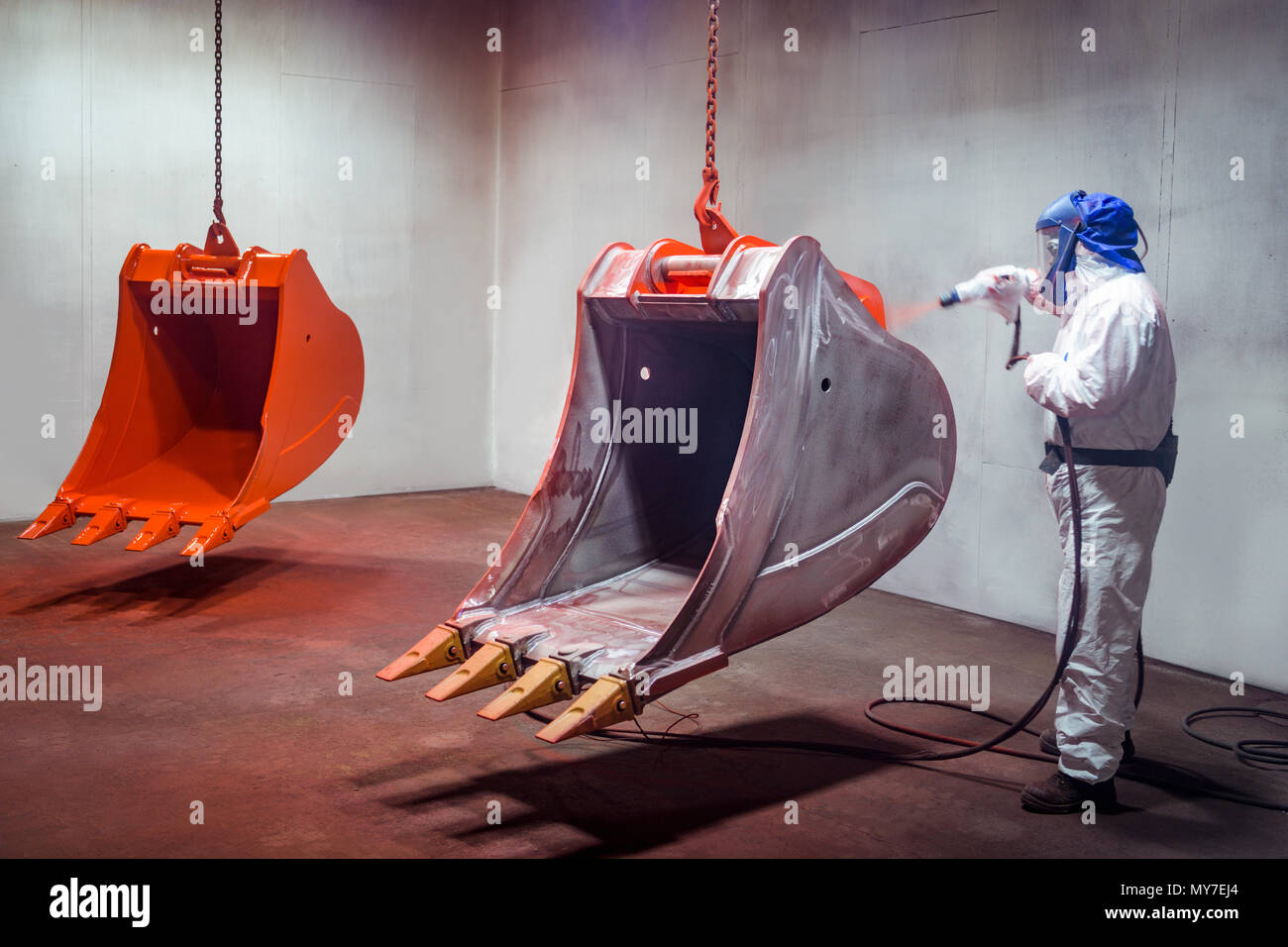 Spray painter painting digger buckets in spray booth in engineering factory - Stock Image