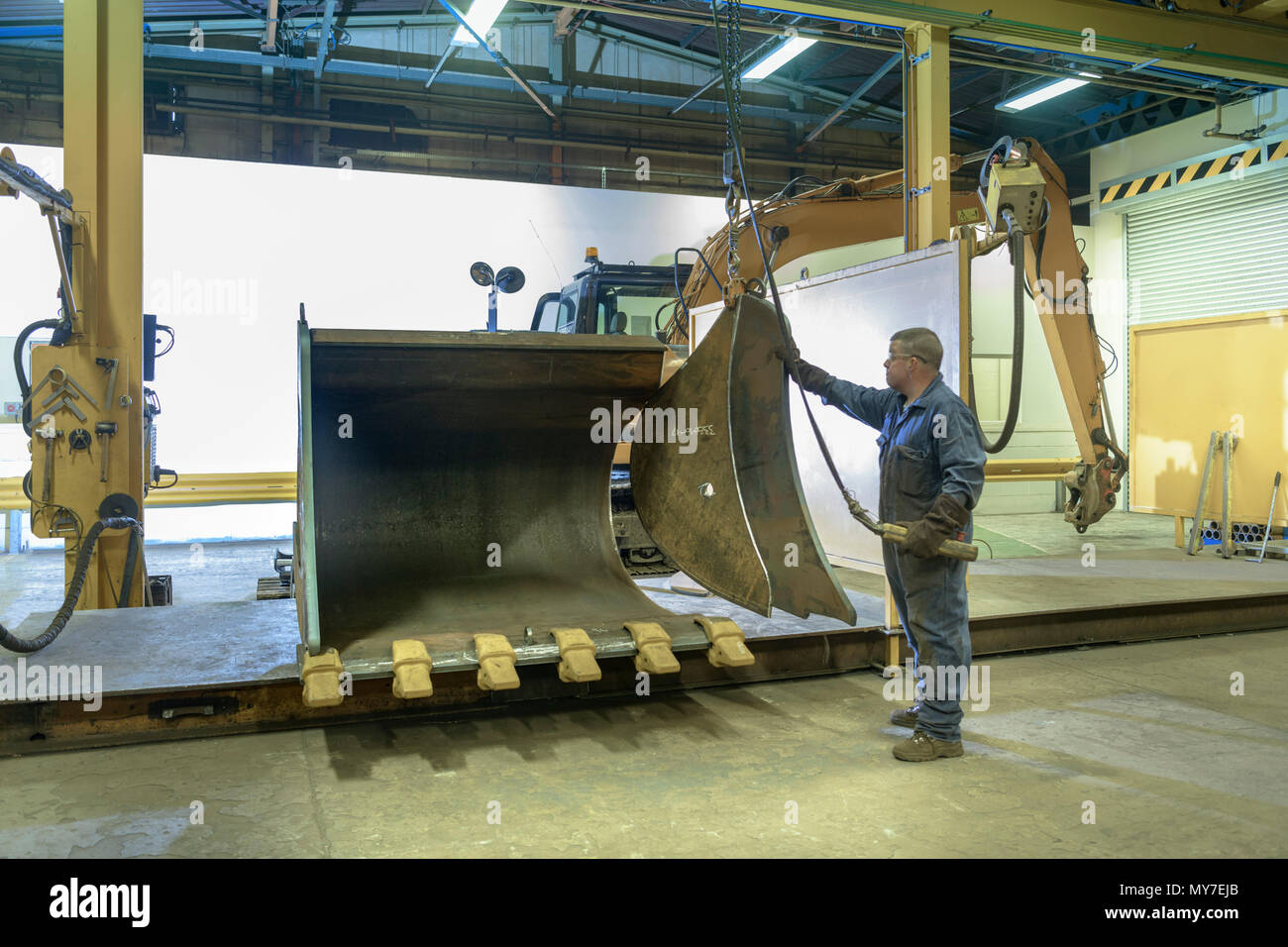 Worker assembling digger bucket in engineering factory - Stock Image