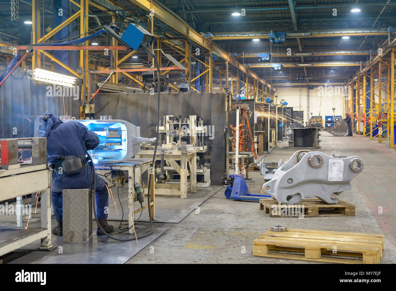 Wide angle view of engineering factory with welder working in foreground - Stock Image