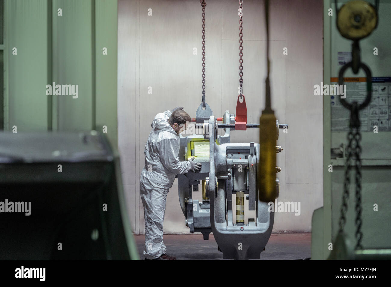 Paint sprayer inspecting product in engineering factory - Stock Image
