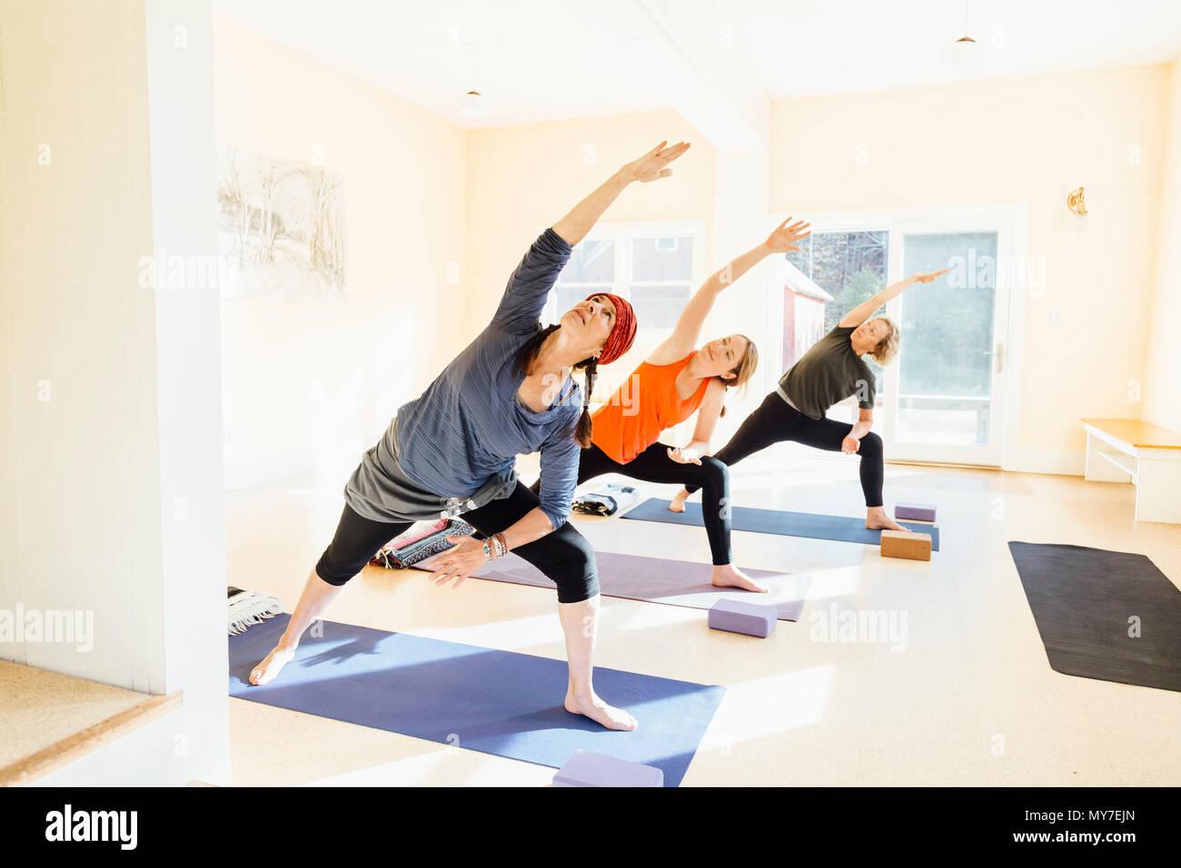 Three women practicing extended side angle lunge, (parsvakonasana) yoga pose in yoga studio - Stock Image