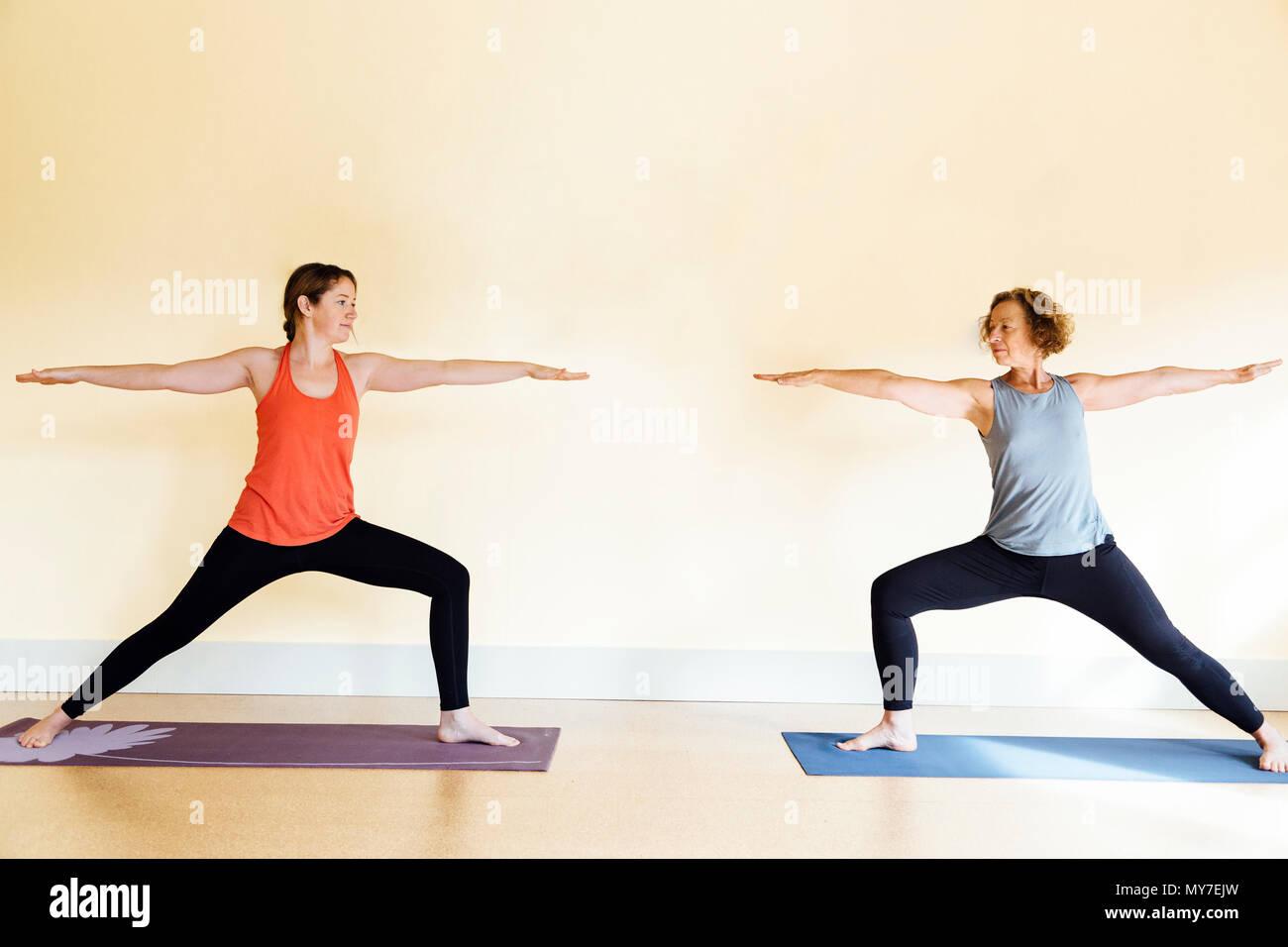 Two women practicing  warrior two (virabhadrasana II) yoga pose in yoga studio Stock Photo
