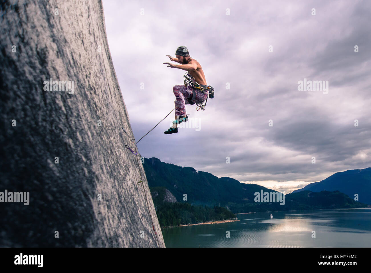Man with climbing rope jumping off rock face on Malamute, Squamish, Canada - Stock Image