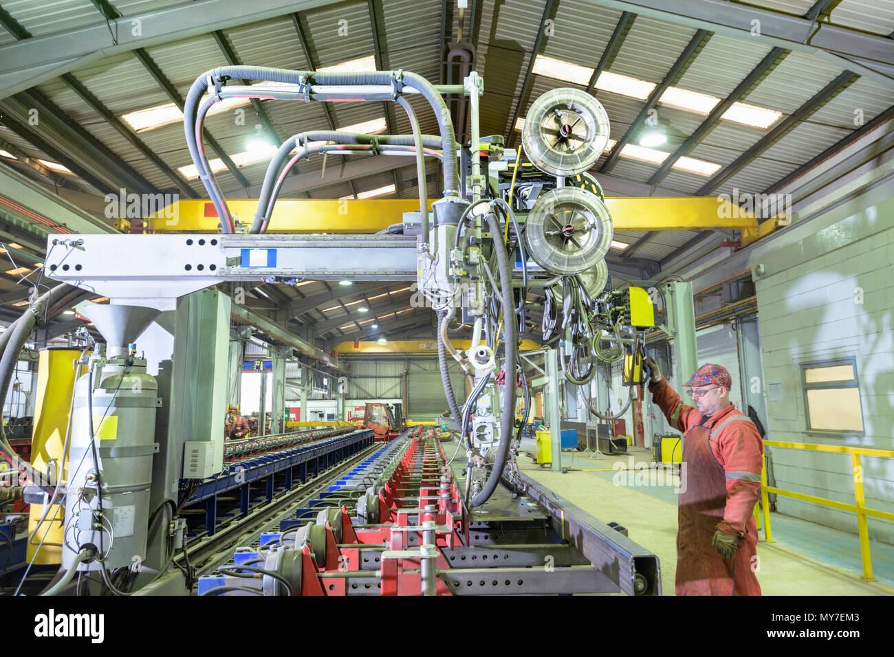 Worker operating beam welding machine in trailer factory - Stock Image
