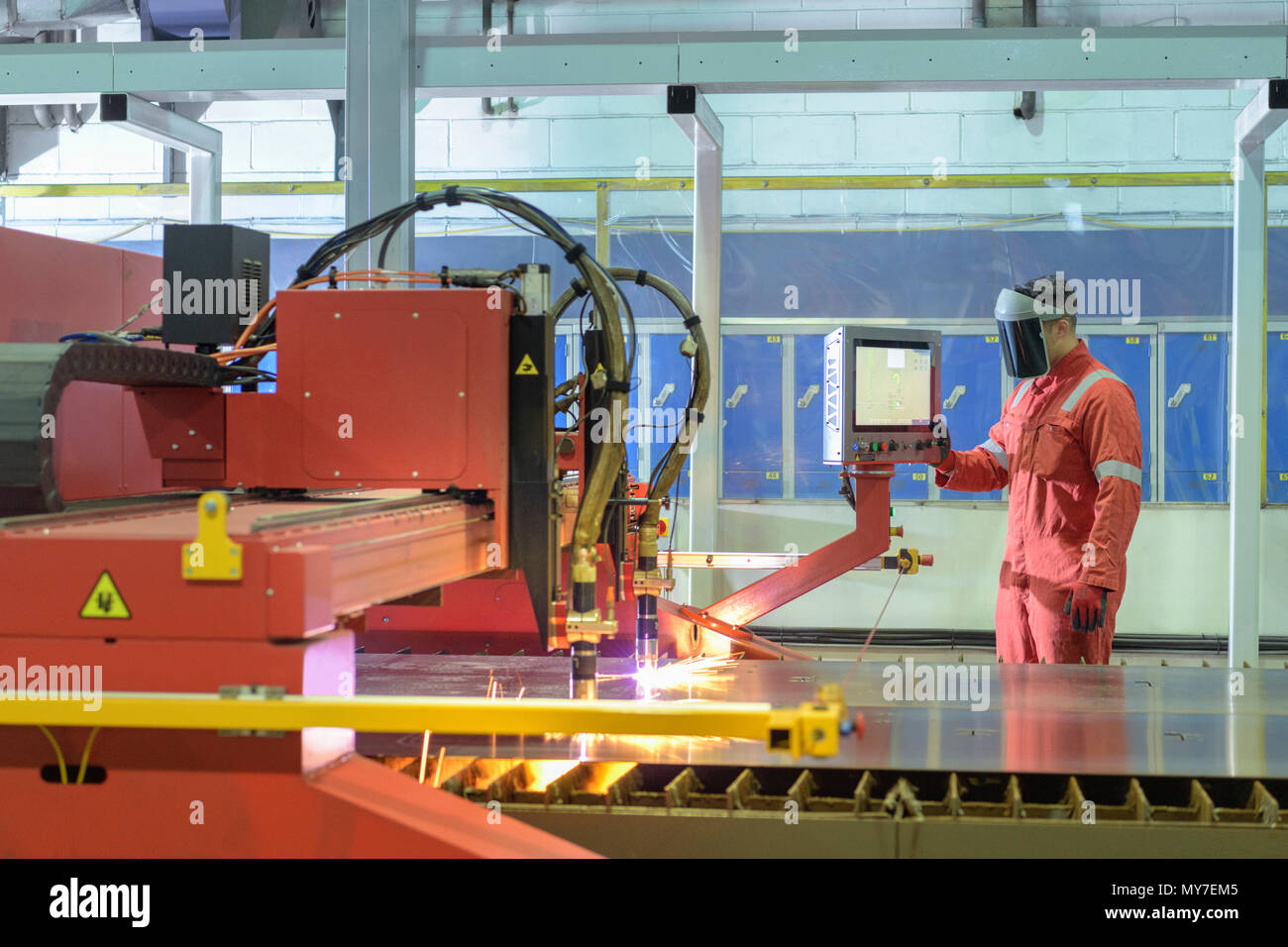 Worker operating plasma cutter in trailer factory - Stock Image