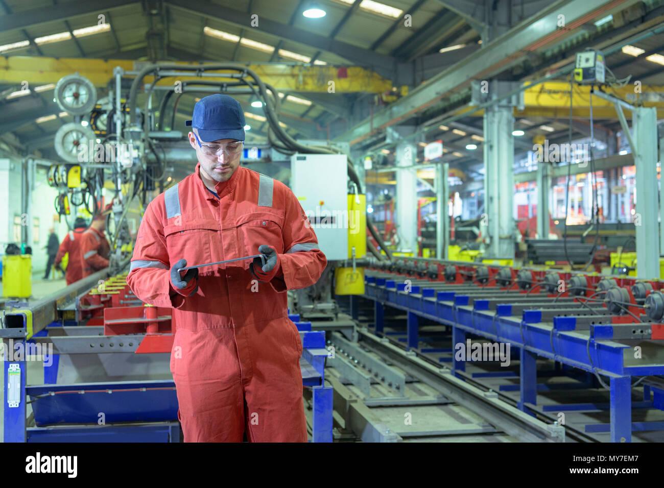 Portrait of worker inspecting metal part in trailer factory - Stock Image