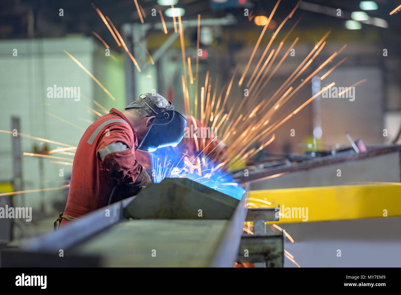 Welder using grinder in trailer factory - Stock Image