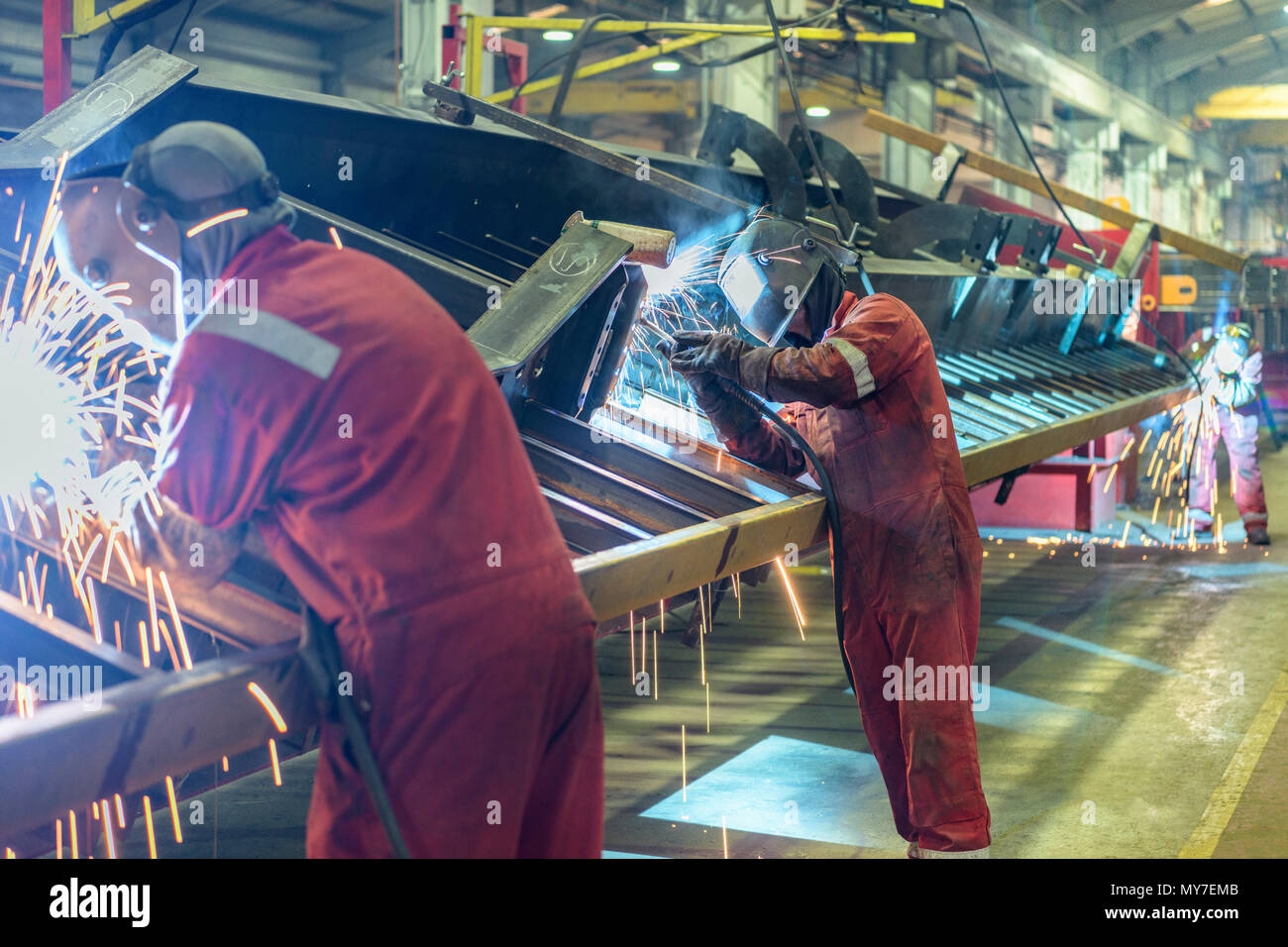 Line of welders working on chassis construction in trailer factory Stock Photo