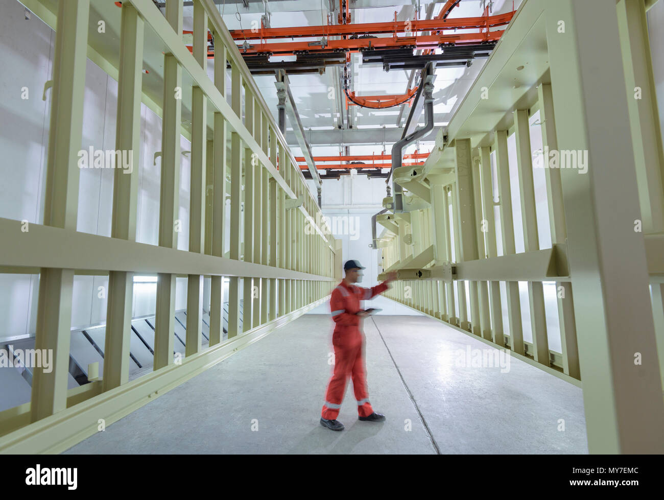 Worker inspecting painted chassis in drying room in trailer factory - Stock Image