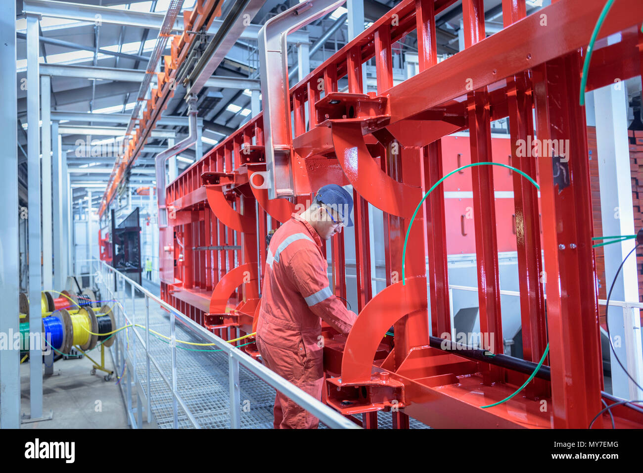 Worker fitting parts to chassis in trailer factor - Stock Image