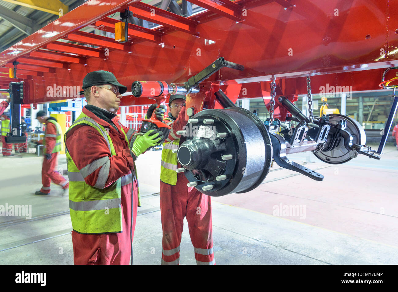 Worker using torque wrench to fix electrical axle to chassis on production line in trailer factory - Stock Image