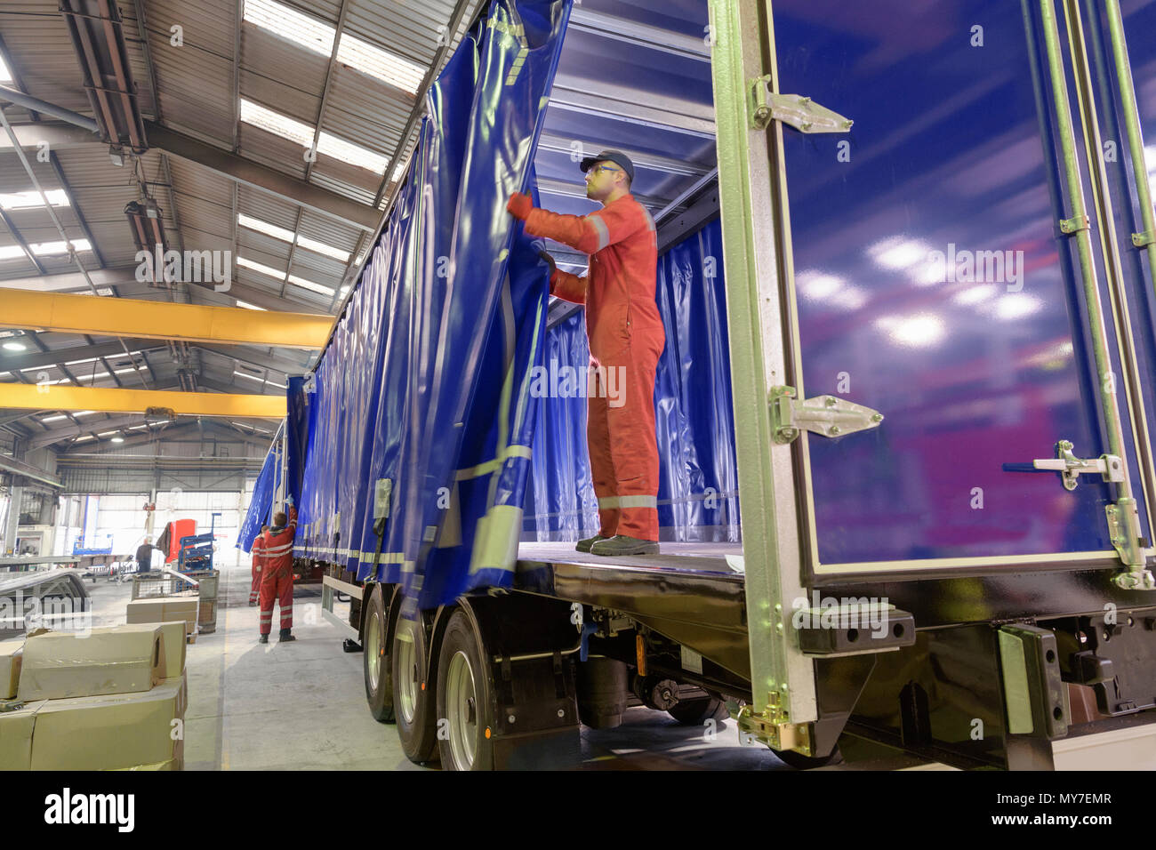 Worker fitting curtain side to trailer on production line in trailer factory - Stock Image