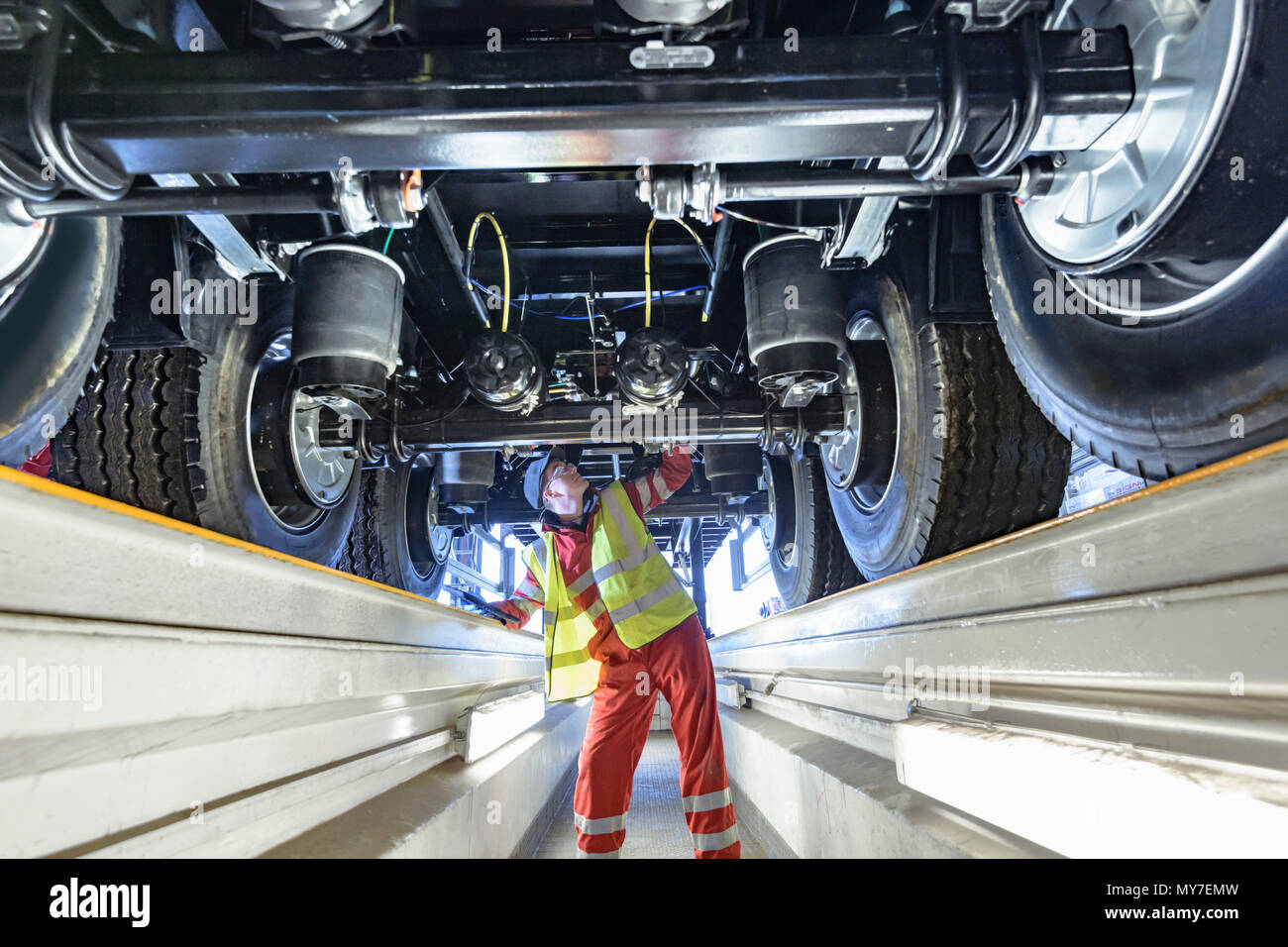 Worker inspecting underside of trailer on production line in trailer factory - Stock Image