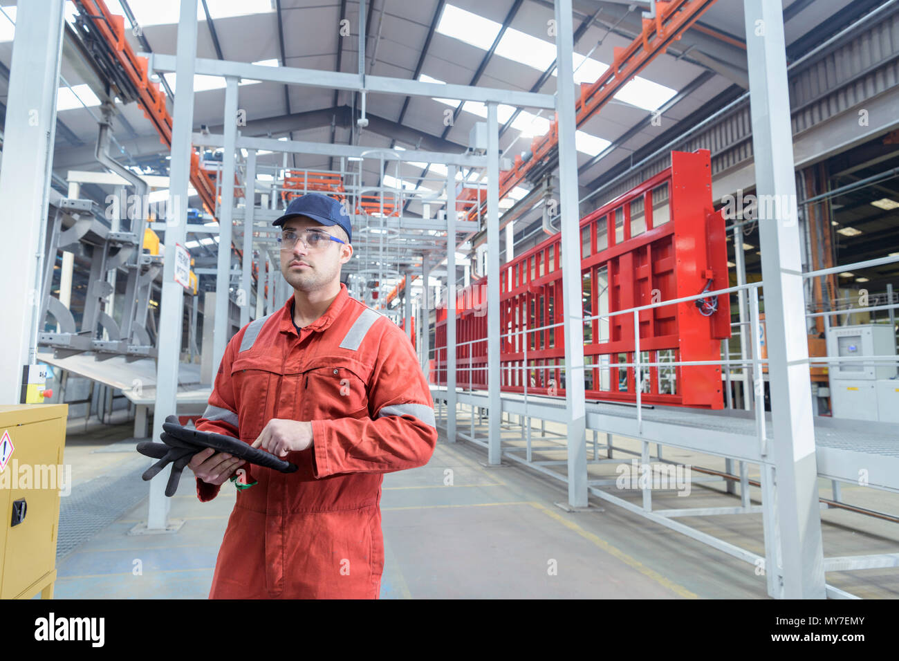 Portrait of worker with digital tablet in trailer factory - Stock Image
