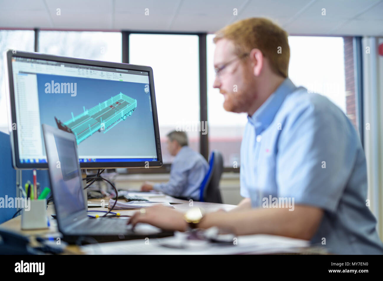 Designers with CAD drawings in trailer factory - Stock Image