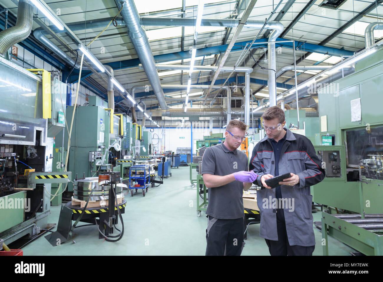 Engineers inspecting pressed metal part in metal pressing factory - Stock Image