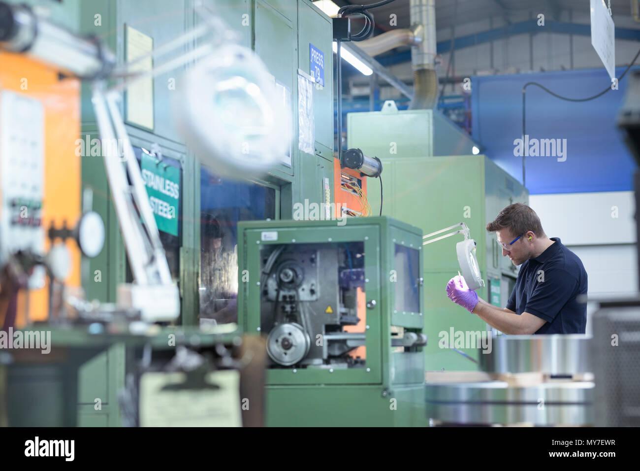 Engineer inspecting pressed metal part in metal pressing factory - Stock Image