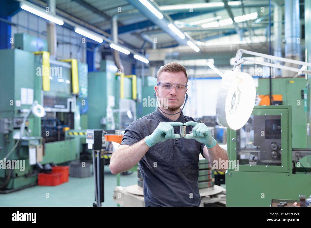 Engineer holding pressed part in metal pressing factory - Stock Image