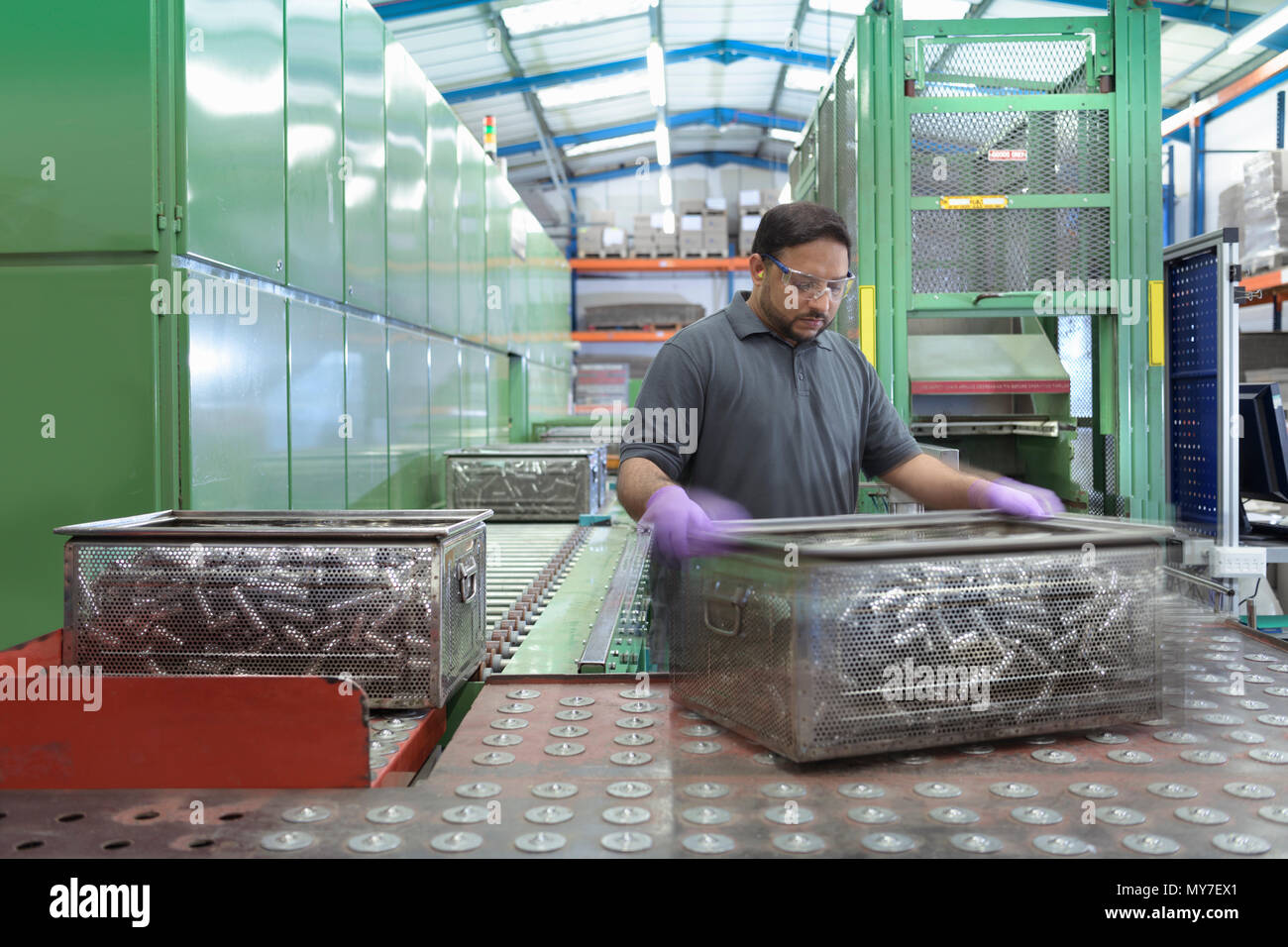 Engineer moving baskets of pressed parts in metal pressing factory - Stock Image