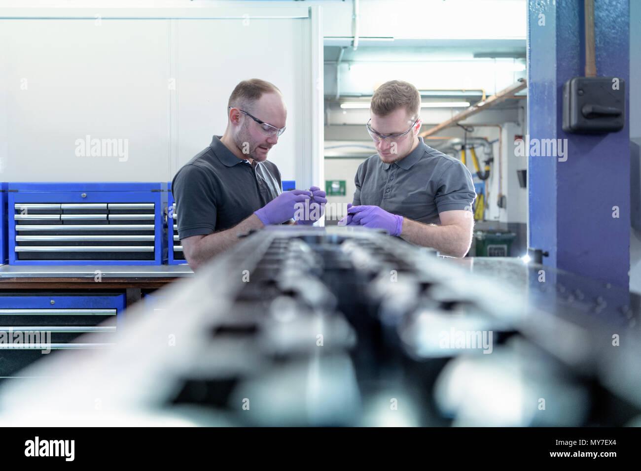 Engineers in tool shop in metal pressing factory - Stock Image