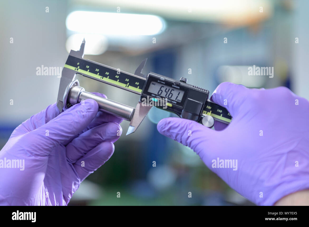 Engineer measuring pressed metal part in metal pressing factory - Stock Image