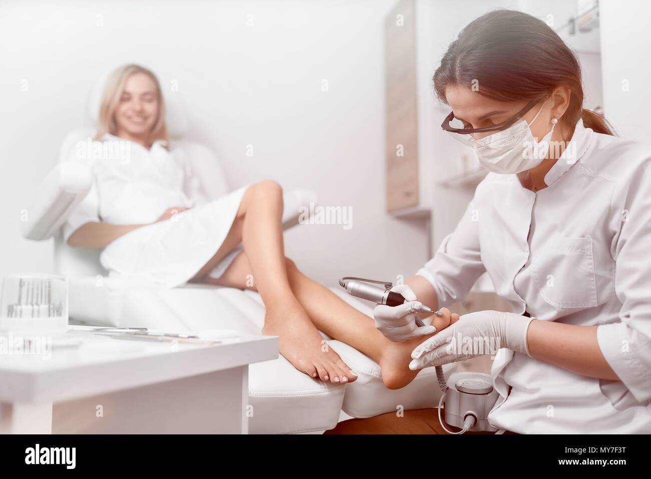 Front view of podiatrist making procedure of grinding for clients feet, cleaning from callus. Happy woman smiling and relaxing in beauty salon. Doctor - Stock Image