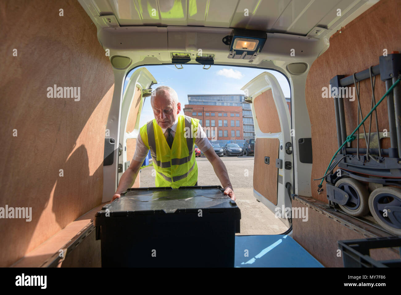 Senior delivery driver loading all electric van - Stock Image