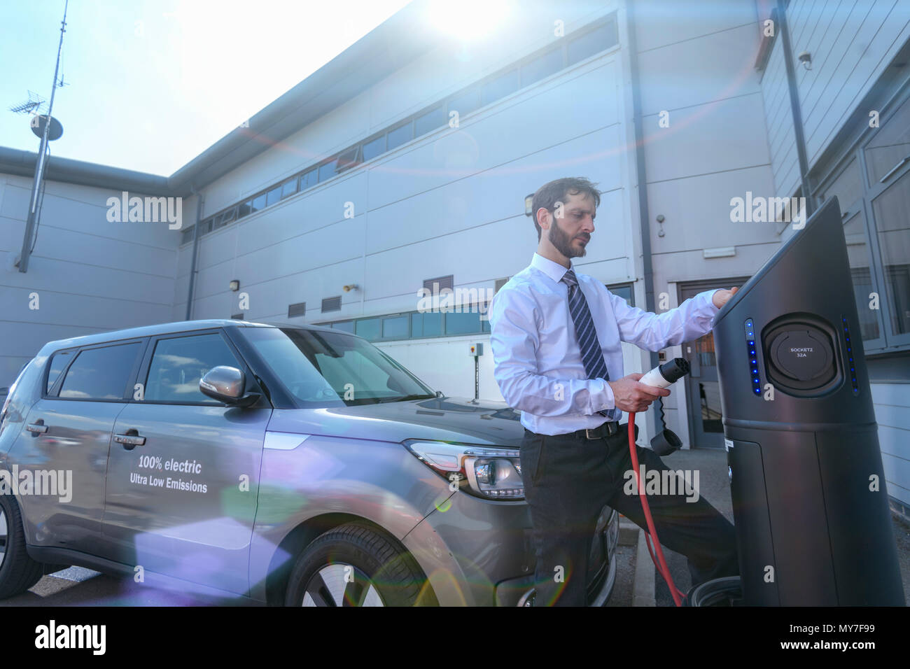 Businessman charging electric car at charging point - Stock Image