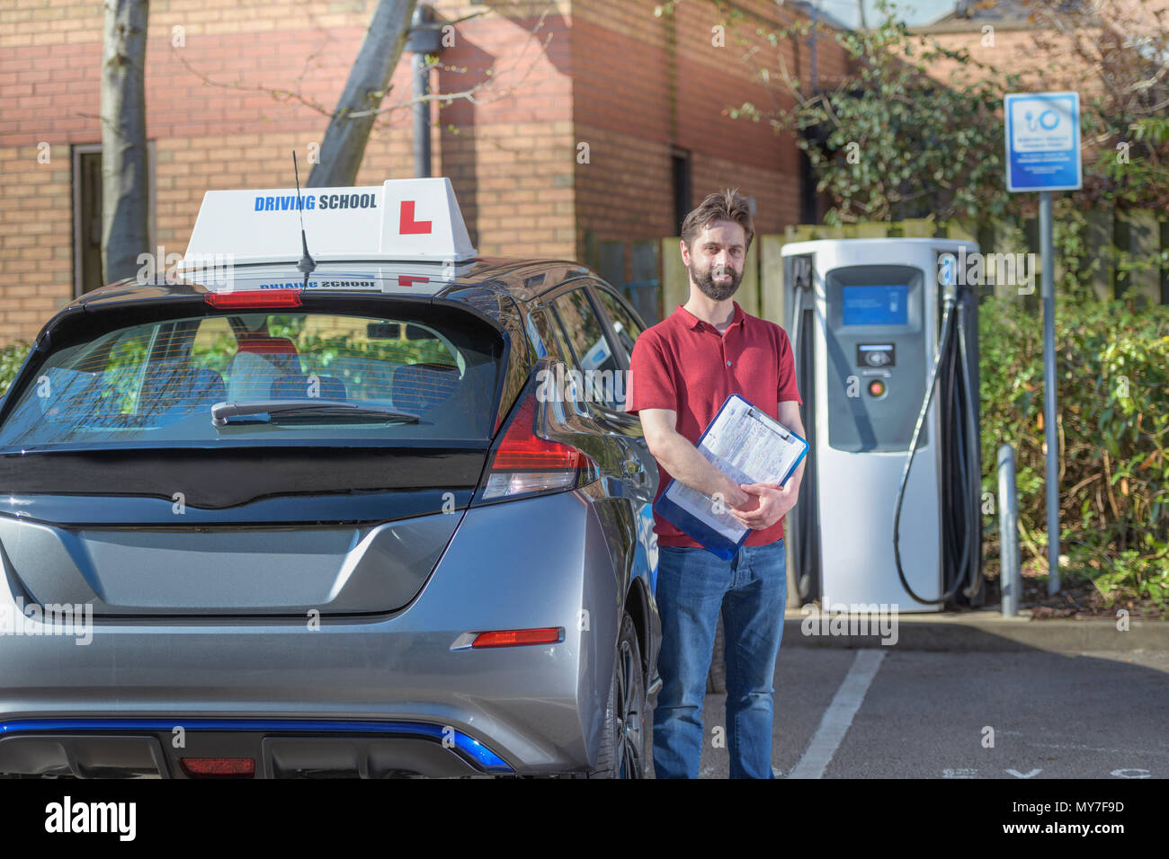 Portrait of driving instructor with electric car at charging point - Stock Image