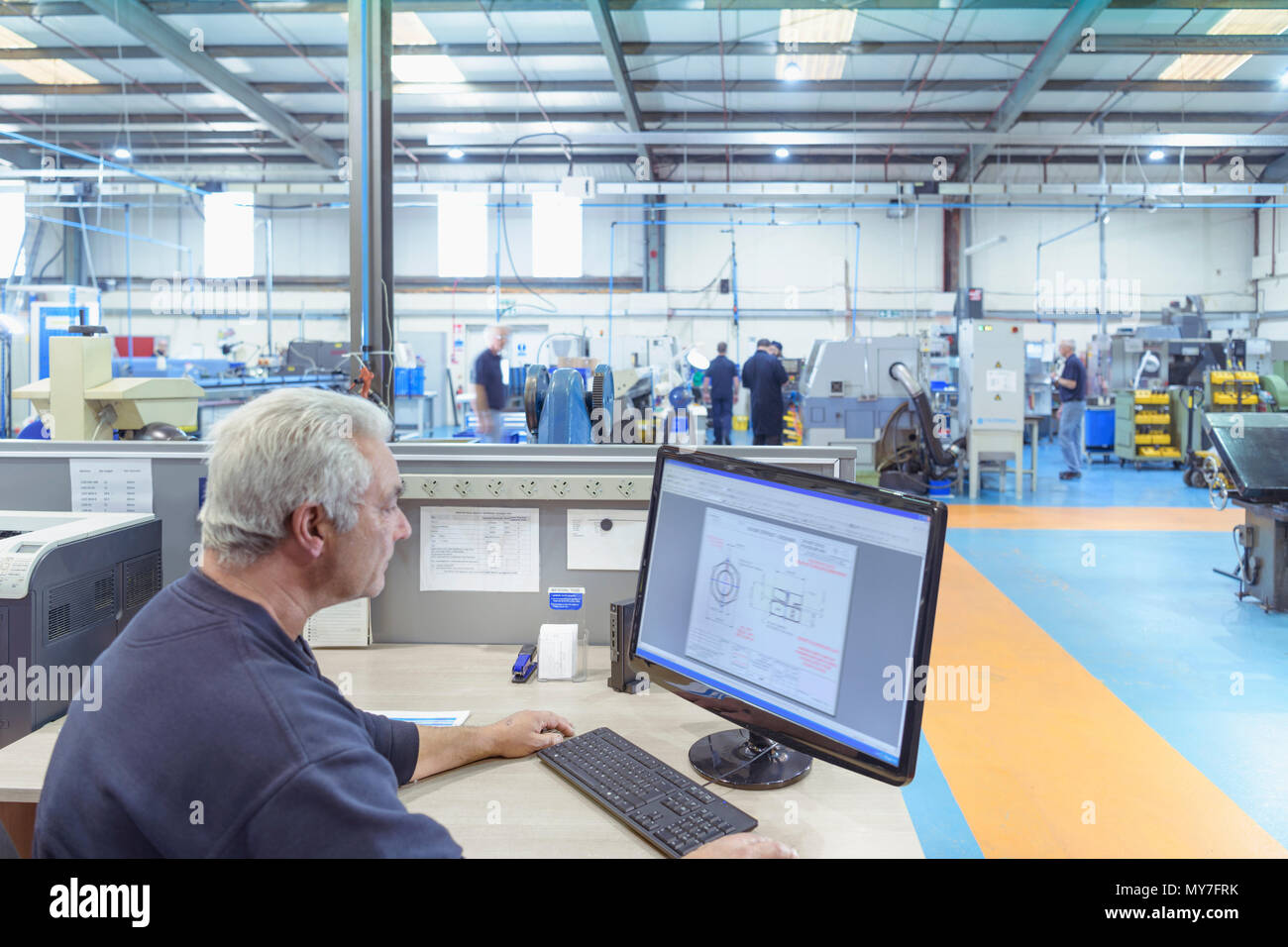 Wide angle view of engineer sending instructions to lathe machinery in engineering factory - Stock Image