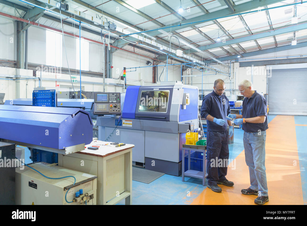 Engineers discussing project work with auto lathe machine in engineering factory - Stock Image