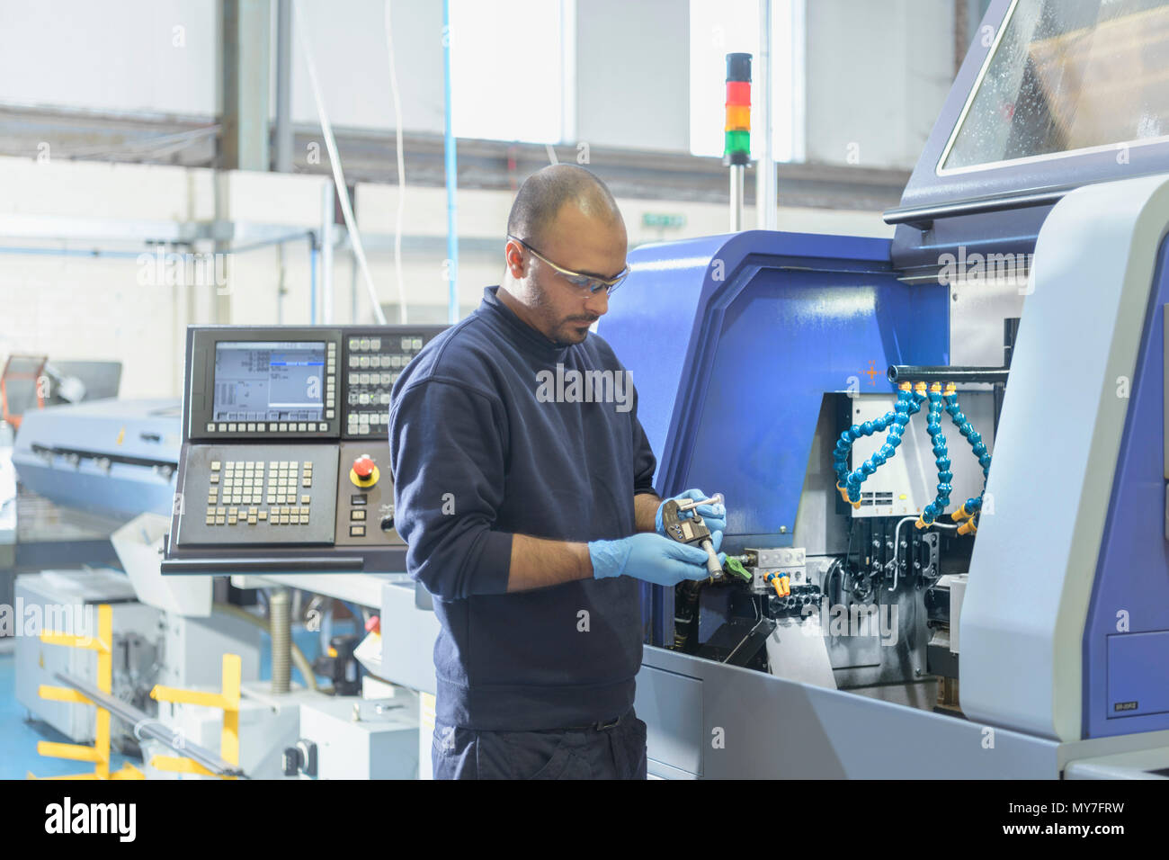Engineer inspecting part for automatic lathe in engineering factory - Stock Image