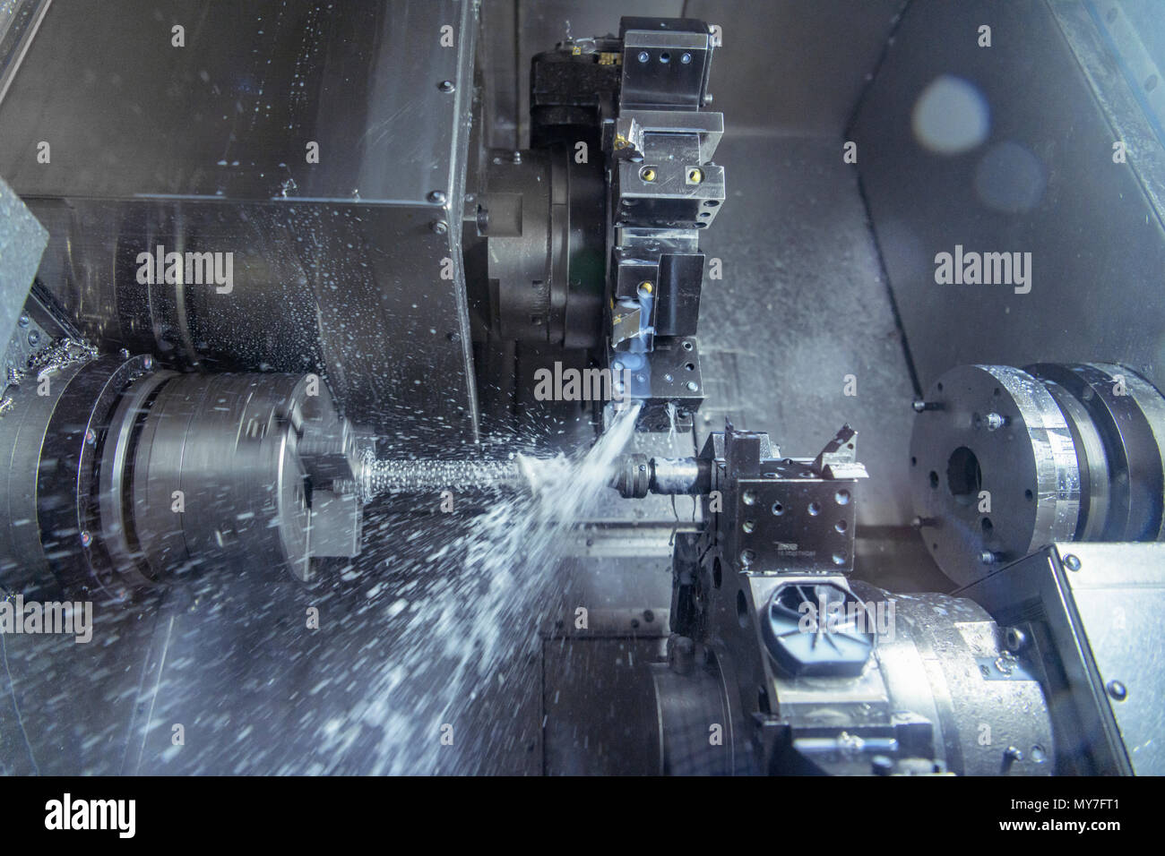 Close up of lathe cutting metal in engineering factory - Stock Image