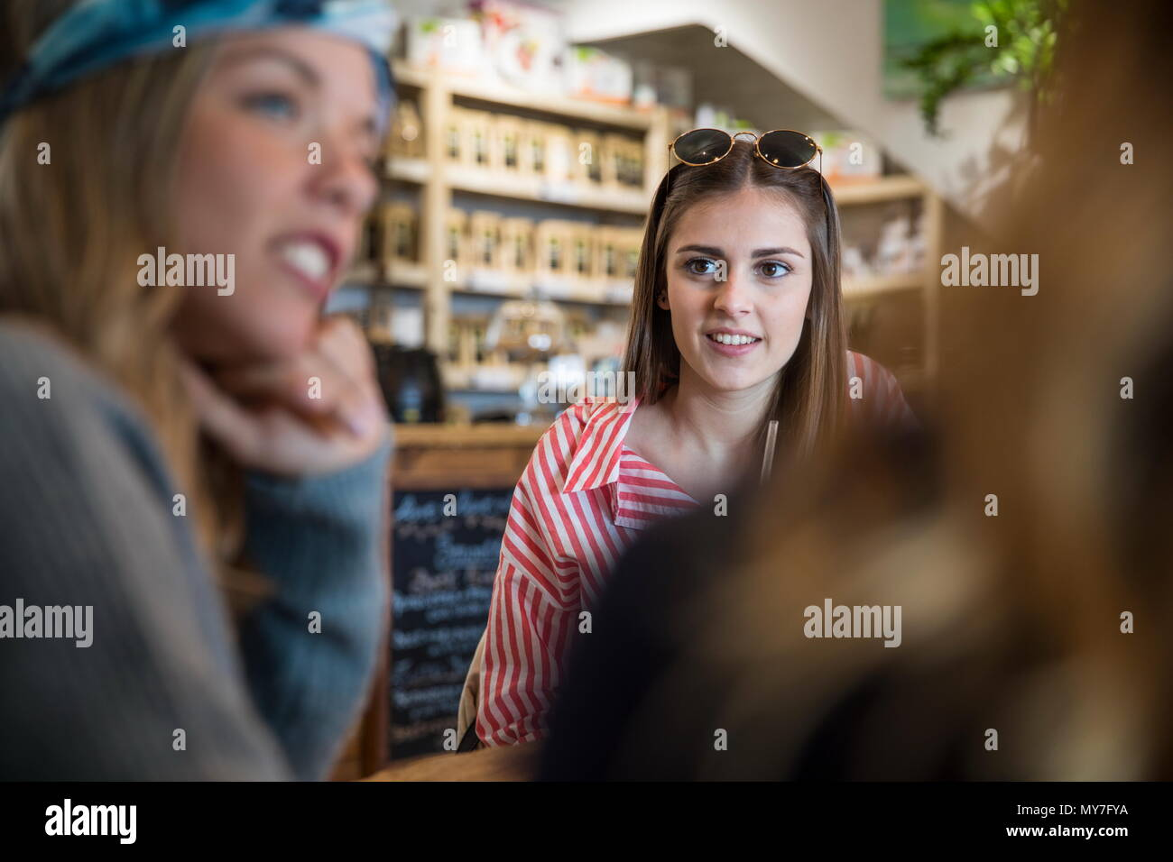 Over shoulder view of three young female friends chatting in cafe - Stock Image