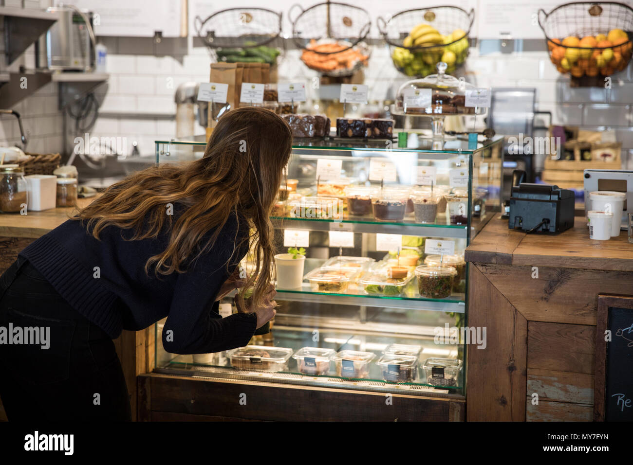 Young woman looking at fresh food display cabinet in cafe - Stock Image