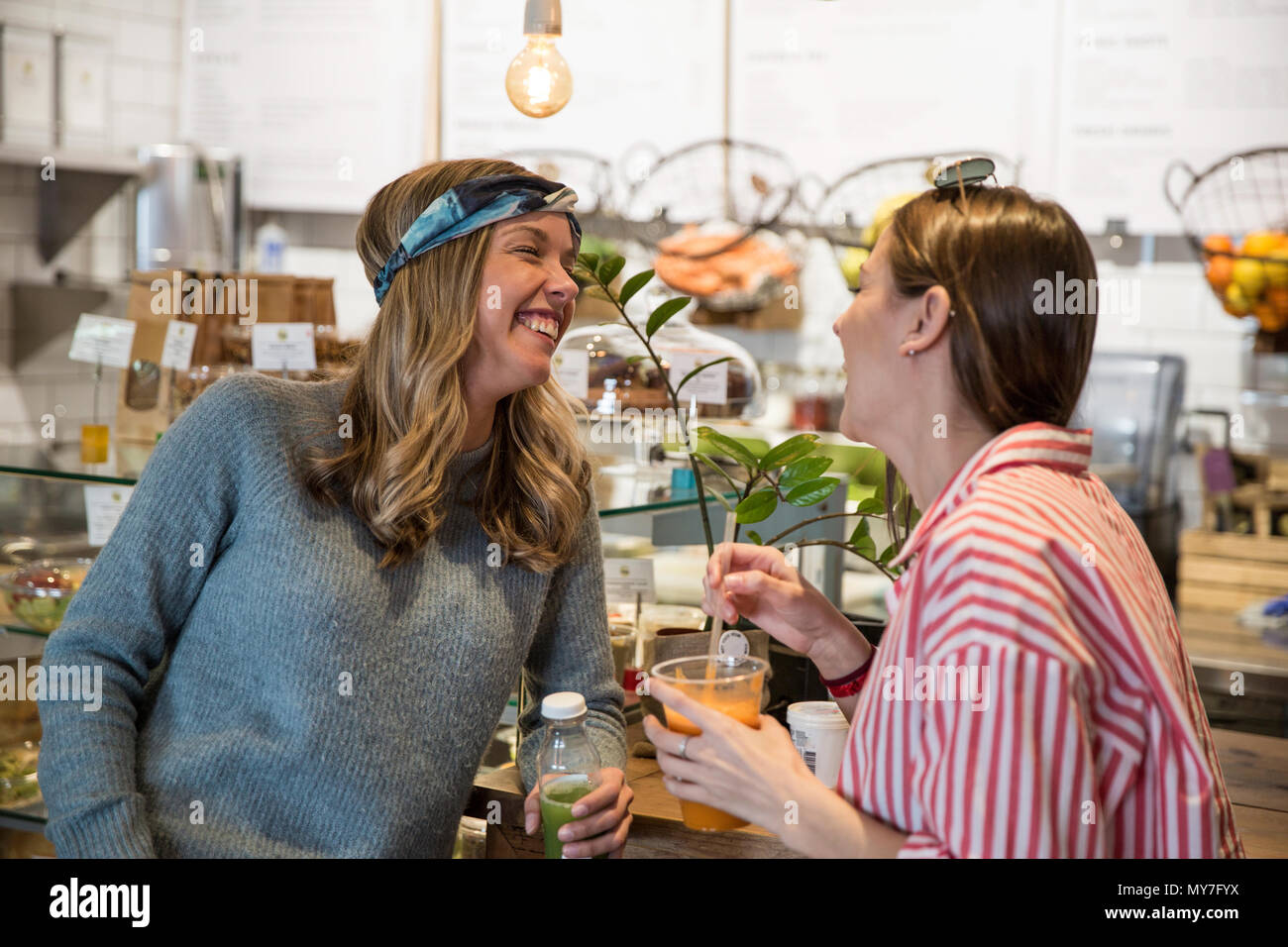 Two young female friends laughing together in cafe - Stock Image