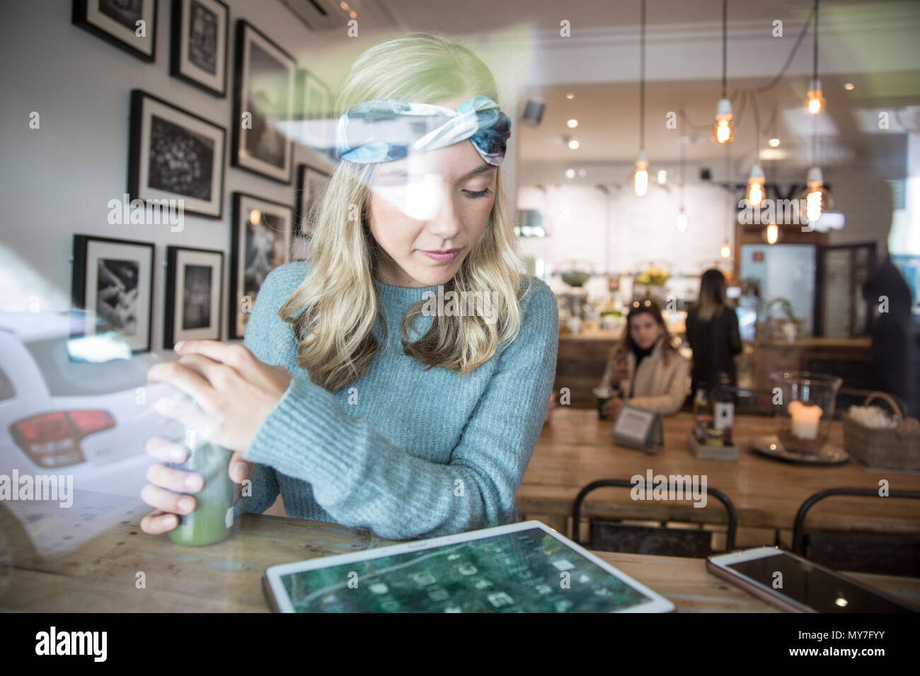 Young woman with vegetable juice looking at digital tablet in cafe window seat - Stock Image