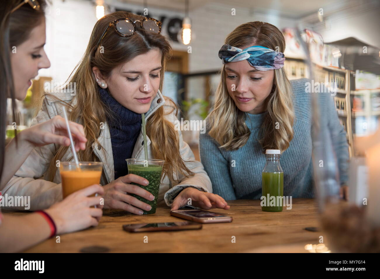 Three female friends, sitting in cafe, drinking smoothies, laughing Stock Photo