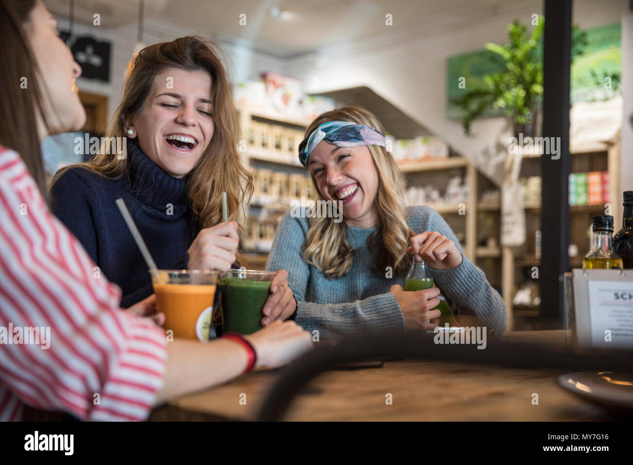Three female friends, sitting in cafe, drinking smoothies, laughing - Stock Image