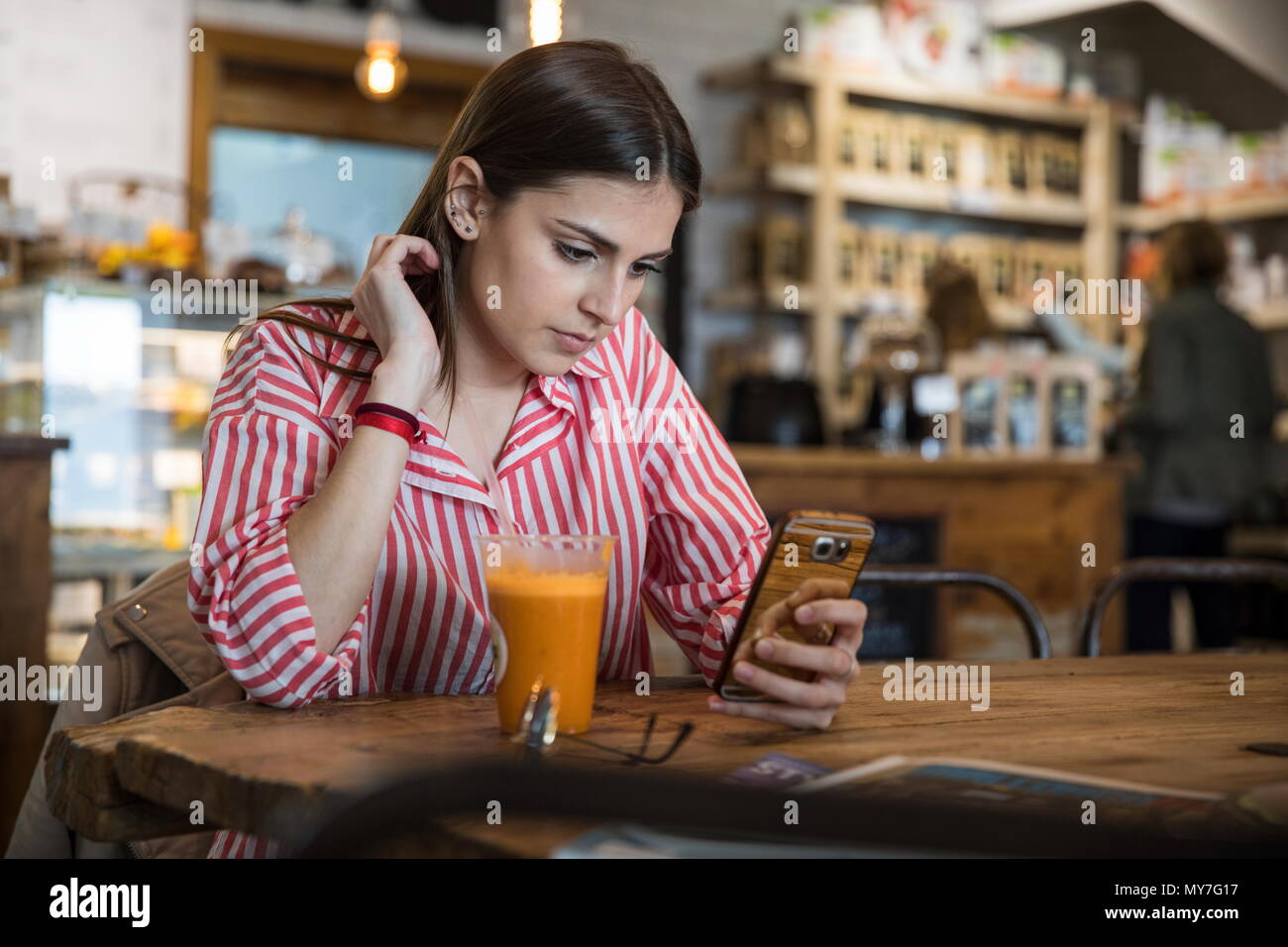 Young woman sitting in cafe, using smartphone, smoothie on table in front of her Stock Photo