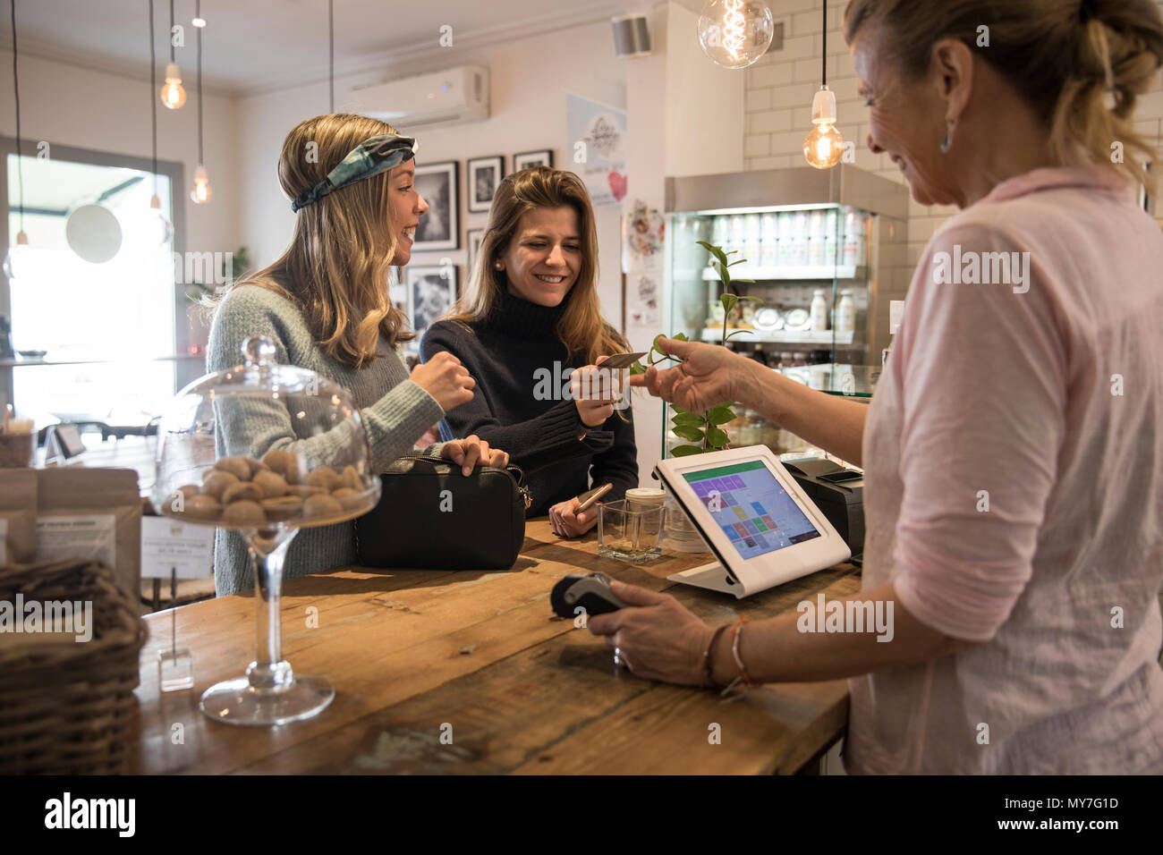 Two female friends, standing at counter in cafe, handing credit card to shop assistant for payment - Stock Image