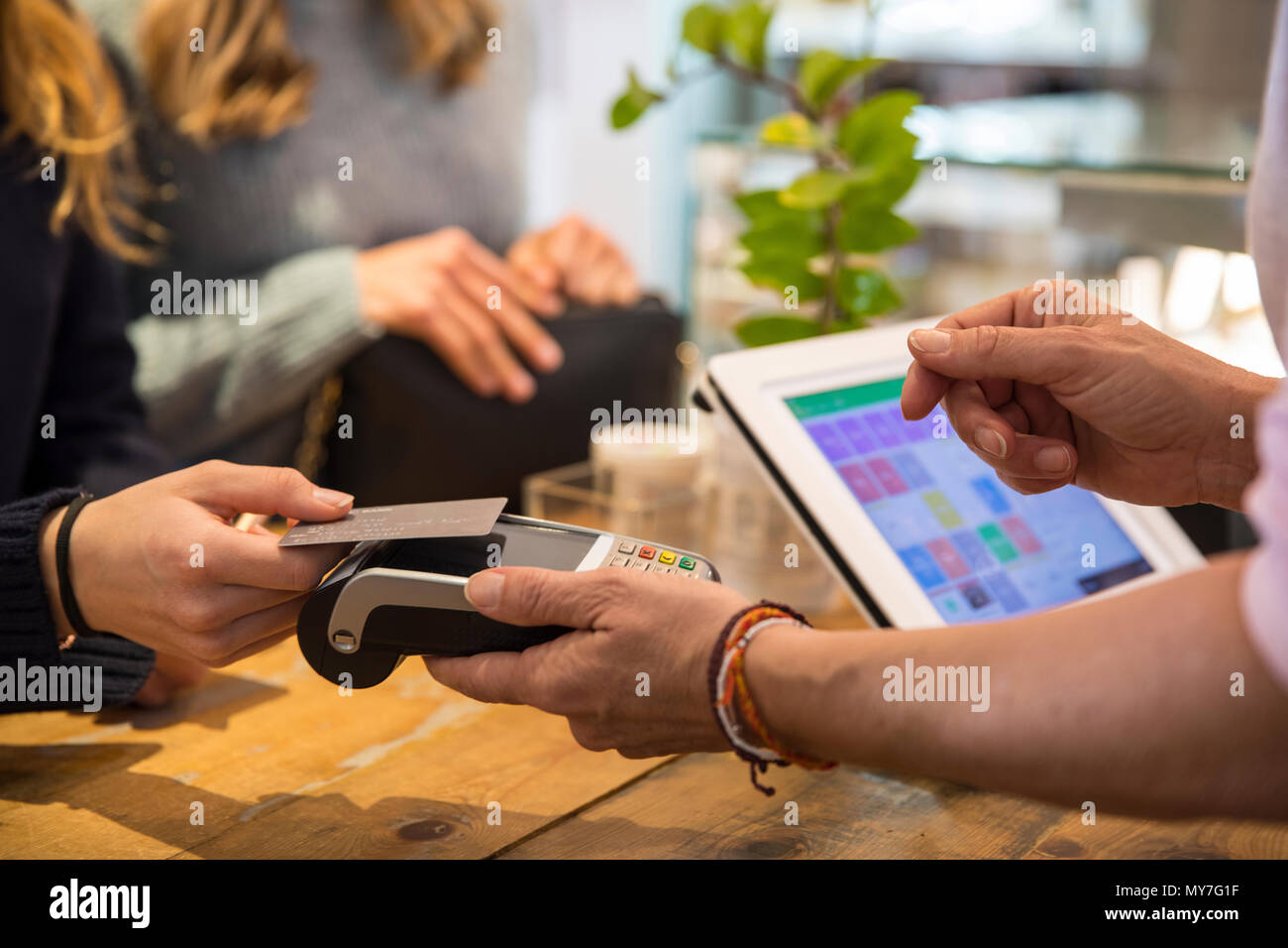 Female customer in shop, paying for goods using credit card on contactless payment machine, mid section, close-up - Stock Image