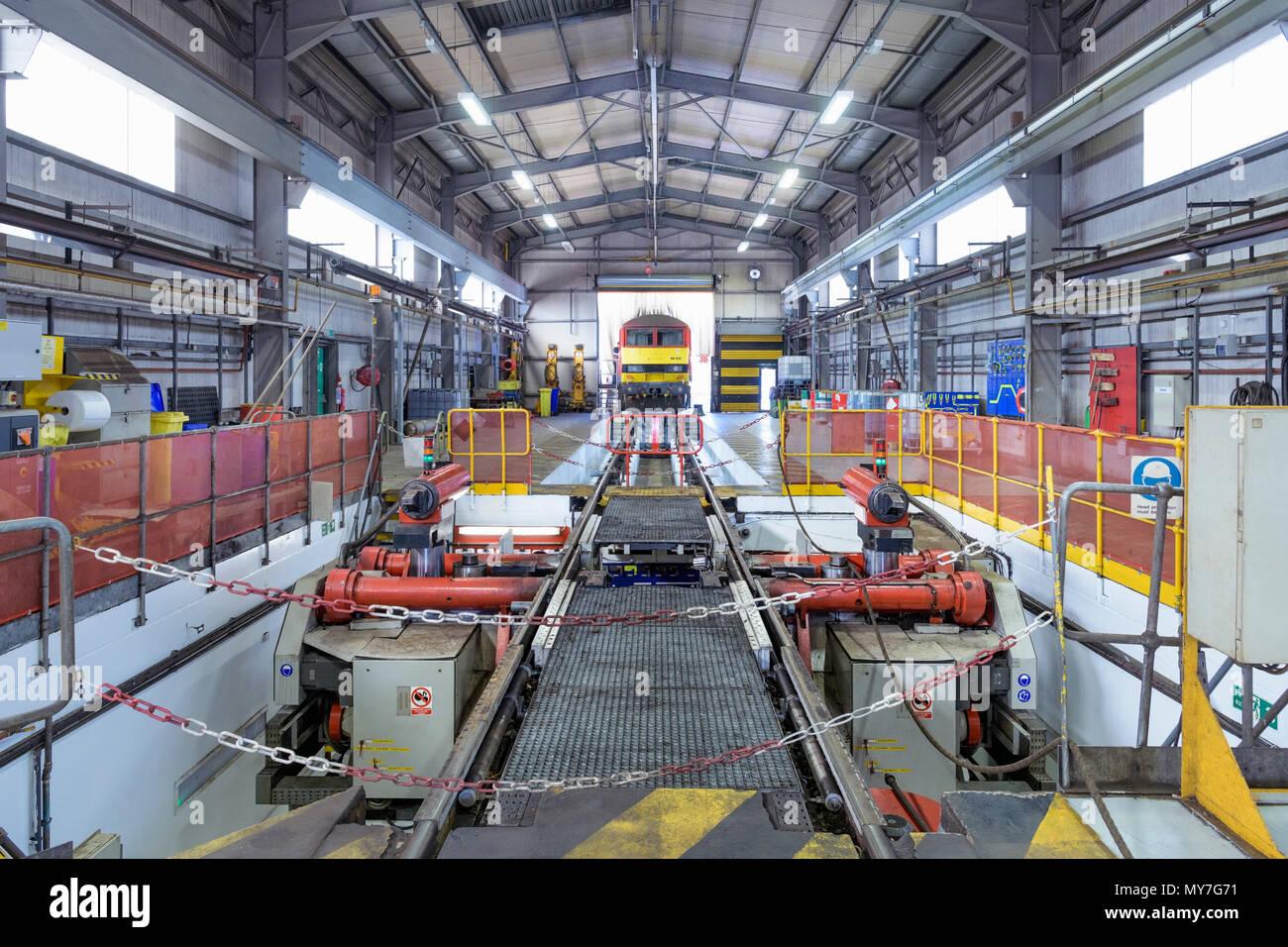 Locomotive approaching wheel lathe machine in train engineering factory - Stock Image
