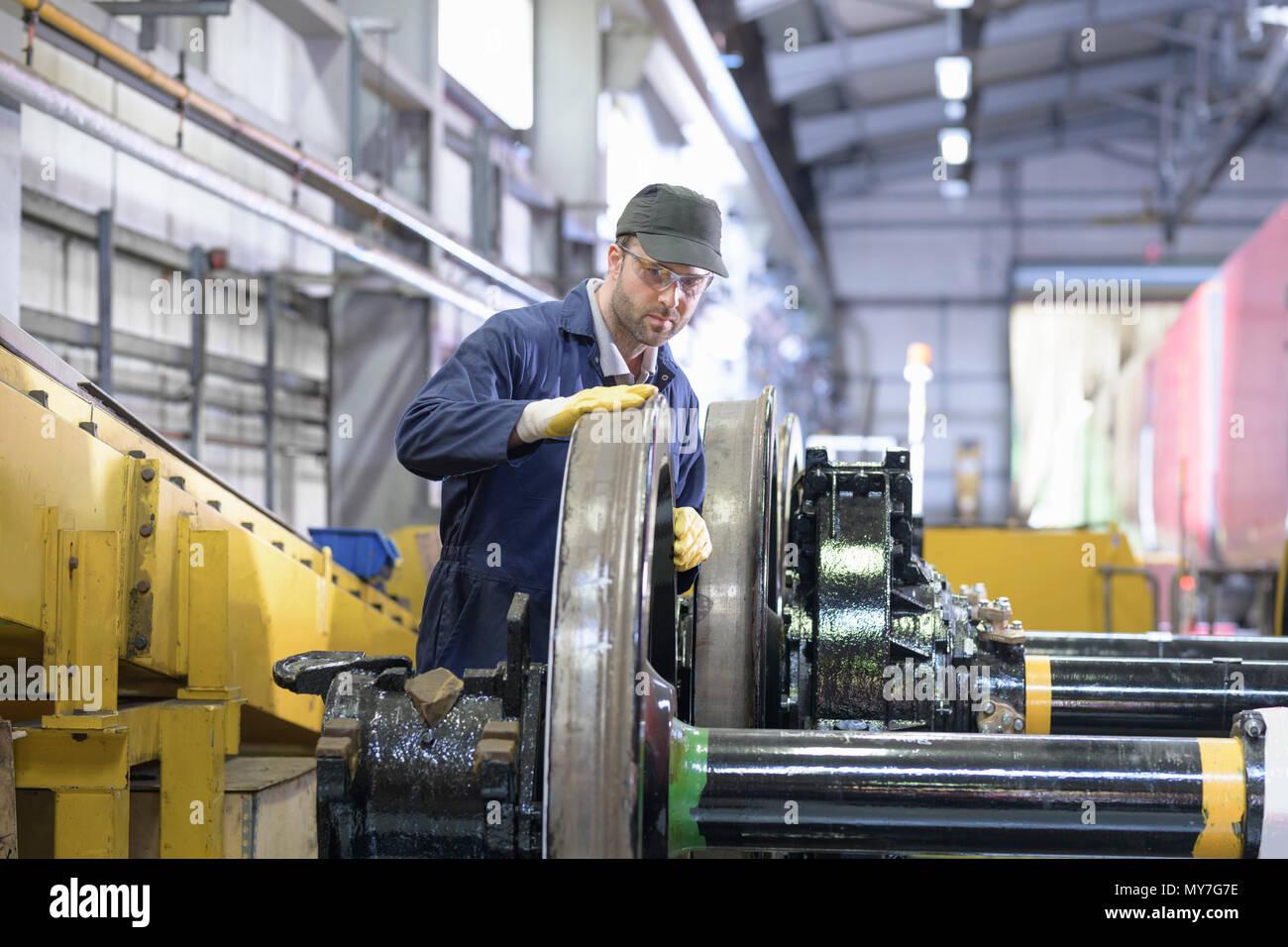 Engineer inspecting locomotive wheels for wear in train engineering factory - Stock Image