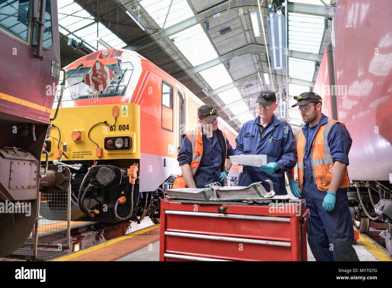 Engineer team discussing project on refurbished locomotive in train engineering factory - Stock Image