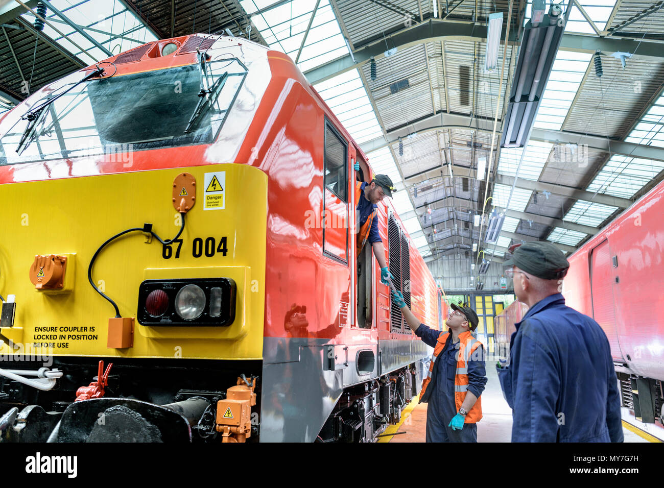 Engineers with refurbished locomotive in train engineering factory - Stock Image