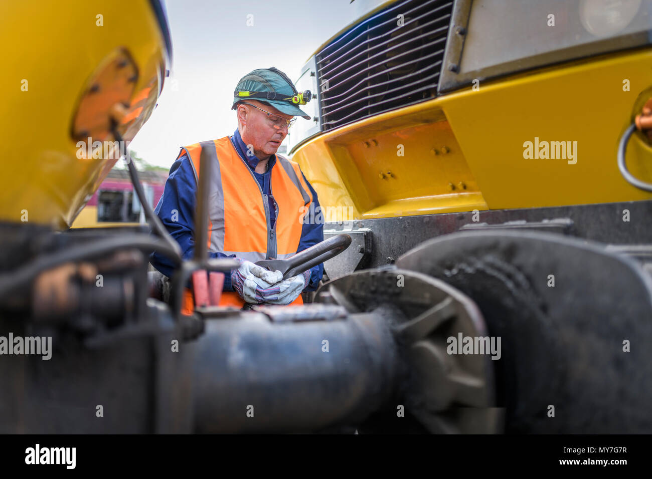 Engineer hitching one locomotive to another in train engineering factory - Stock Image