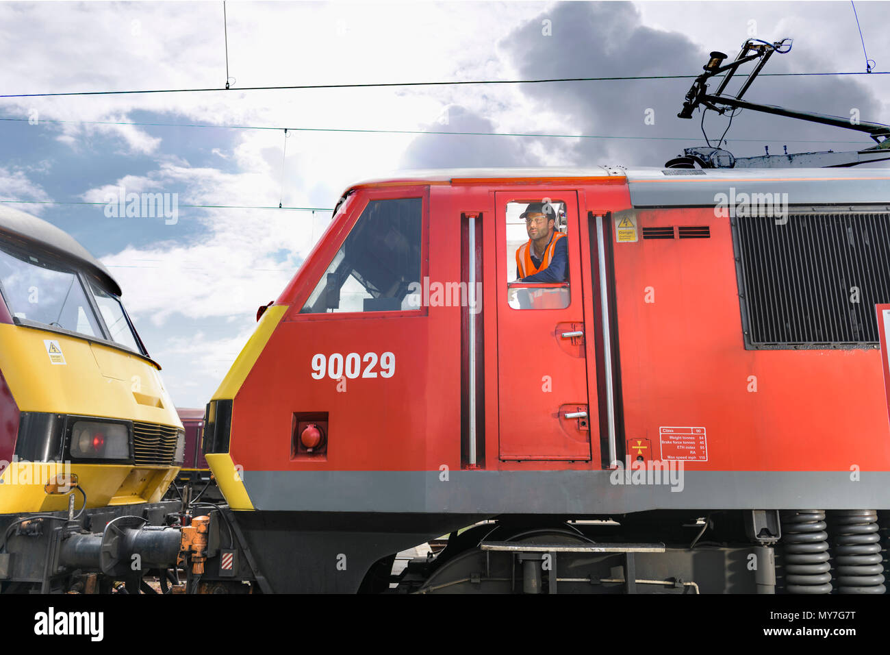 Train driver in locomotive cab in train engineering factory - Stock Image