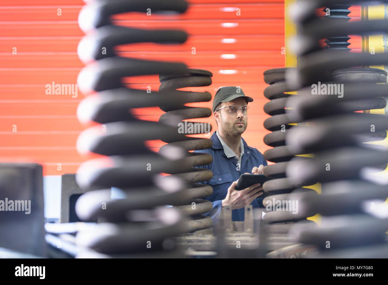 Engineer inspecting springs in train engineering factory - Stock Image